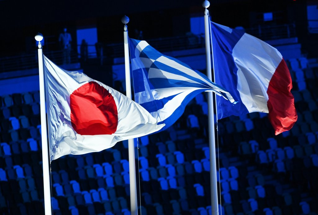 The flags of Japan, Greece and France waves in the Olympic Stadium during the Closing Ceremony of the Tokyo Olympics, Aug. 8, 2021, Tokyo.