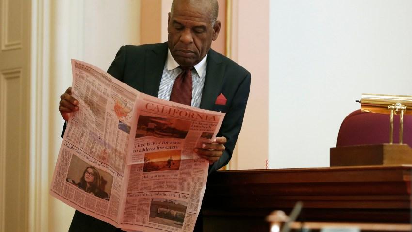 State Sen. Steven Bradford looks at newspaper