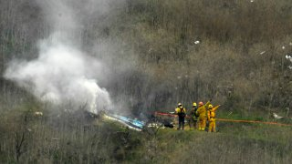 Firefighters work the scene of a helicopter crash