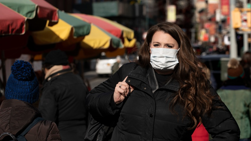 """A woman, who declined to give her name, wears a mask, Thursday, Jan. 30, 2020 in New York. She works for a pharmaceutical company and said she wears the mask out of concern for the coronavirus. """"I'd wear a mask if I were you,"""" she said. For the first time in the U.S., the new virus from China has spread from one person to another, health officials said Thursday. (AP Photo/Mark Lennihan)"""