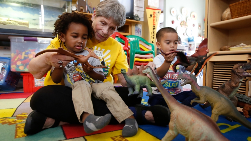 Child care provider Pat Alexander helps children, Isaiah, left, and Hector, right, identify various types of dinosaurs at her child care center in Elk Grove, Calif., on Wednesday, Feb. 26, 2020.
