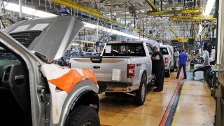United Auto Workers assemblymen work on a 2018 Ford F-150 trucks being assembled at the Ford Rouge assembly plant in Dearborn, Mich.