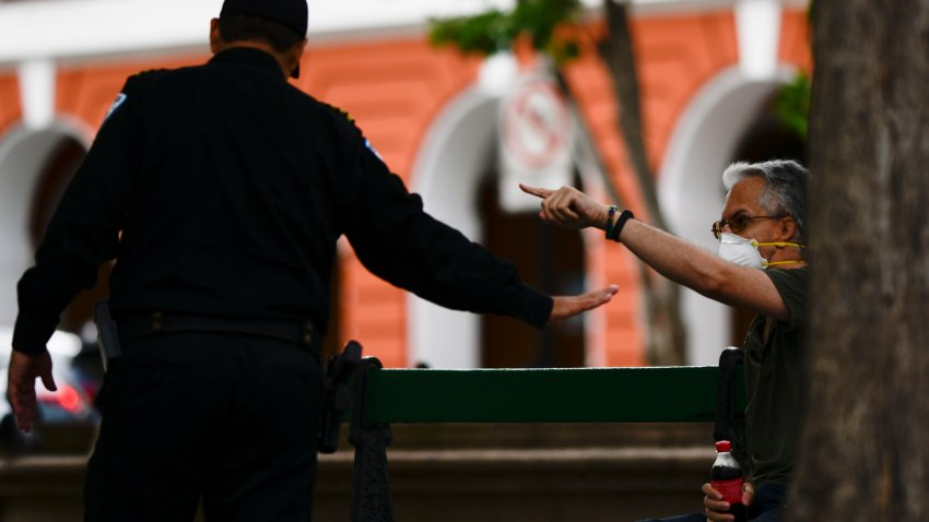 Gustavo Cuevas del Valle, right, who lives on Luna street in Old San Juan, argues with a police officer that asked him not to occupy the benches during a lock down imposed by the government to prevent a spread of the new coronavirus in San Juan, Puerto Rico, Tuesday, March 17, 2020.