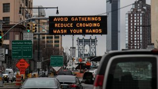 The Manhattan bridge is seen in the background of a flashing sign urging commuters to avoid gatherings, reduce crowding and to wash hands in the Brooklyn borough of New York