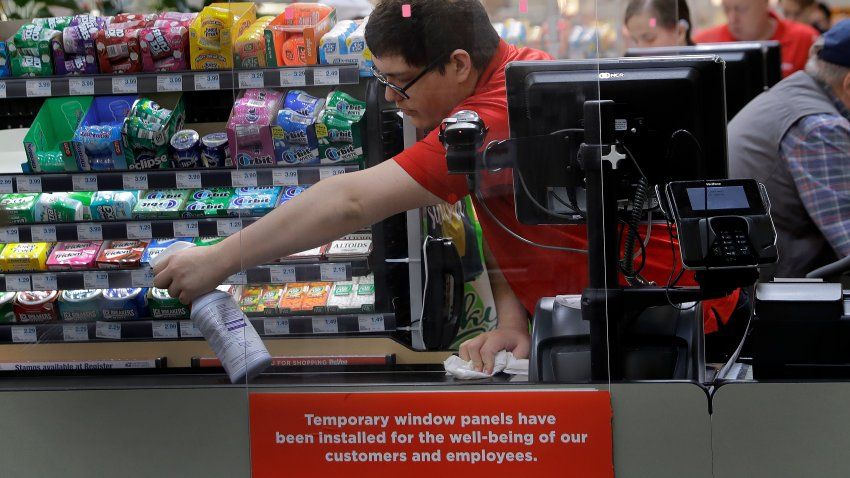 Garrett Ward sprays disinfectant on a conveyor belt between checking out shoppers behind a plexiglass panel at a Hy-Vee grocery store in Overland Park, Kan.