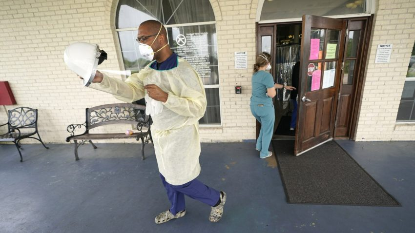 Dr. Robin Armstrong puts on his face shield while demonstrating his full personal protective equipment outside the entrance to The Resort at Texas City nursing home, where he is the medical director, Tuesday, April 7, 2020, in Texas City, Texas.