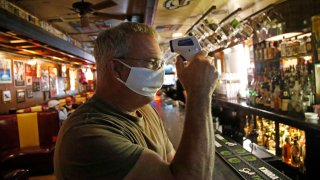 Cheers to You bar owner Bob Brown tests a thermometer at his bar Friday, May 1, 2020, in Salt Lake City.