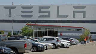 A masked man walks in the Tesla plant parking lot Monday, May 11, 2020, in Fremont, Calif.