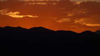 Clouds are illuminated from below as the sun sets behind the Rocky Mountains while residents remain indoors despite the lifting of many restrictions to stop the rise of the new coronavirus late Tuesday, May 19, 2020, in Denver.
