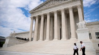 In this May 14, 2020, file photo security officers walk in front of the Supreme Court in Washington.