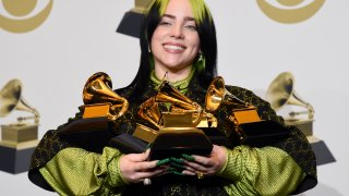 """FILE - In this Jan. 26, 2020 file photo, Billie Eilish poses in the press room with the awards for best album and best pop vocal album for """"We All Fall Asleep, Where Do We Go?"""", best song and record for """"Bad Guy"""" and best new artist at the 62nd annual Grammy Awards in Los Angeles. The Recording Academy is making changes to several Grammy Awards categories, including the often-debated best new artist title, as well as having nomination review committee members sign disclosure forms to prevent conflicts of interest."""