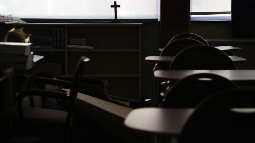 A cross sits in the window of an empty classroom at Quigley Catholic High School in Baden, Pa.
