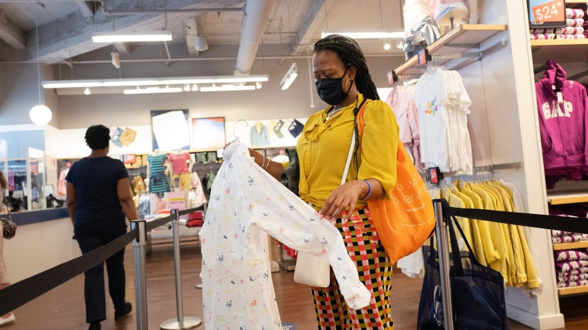 FILE - In this Tuesday, June 30, 2020, file photo, a woman shops for clothing in a Gap store during the coronavirus pandemic, in New York.