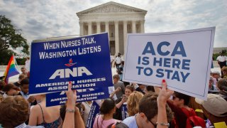 In this June 25, 2015, file photo, supporters of the Affordable Care Act hold up signs as the opinion for health care is reported outside of the Supreme Court in Washington, DC.