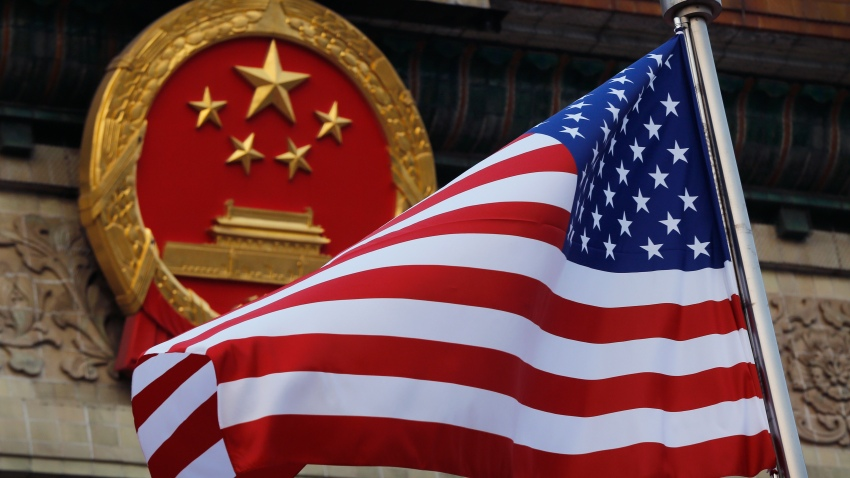 In this Nov. 9, 2017 file photo, an American flag is flown next to the Chinese national emblem during a welcome ceremony for visiting U.S. President Donald Trump outside the Great Hall of the People in Beijing.