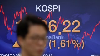In this April 9, 2020, file photo, currency trader walks by the screen showing the Korea Composite Stock Price Index (KOSPI) at the foreign exchange dealing room in Seoul, South Korea.
