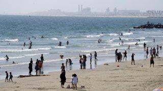 People visit the beach Sunday, May 24, 2020, in Newport Beach, Calif., during the coronavirus pandemic.