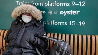 A traveller wears a mask as he waits at Victoria Station in London, Monday, March 16, 2020.