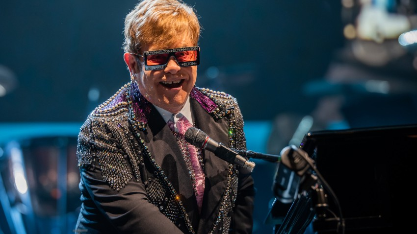 """Elton John is hosting a """"living room"""" concert aimed at bolstering American spirits during the coronavirus crisis and saluting those countering it."""