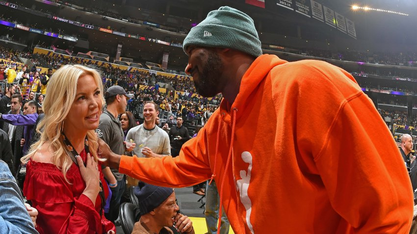Kobe Bryant speaks with Lakers President Jeanie Buss during a game.