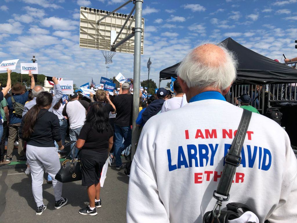 """Jeff Jones, 77, wearing his """"I am not Bernie Sanders"""" sweater, attends a Bernie Sanders rally at a Santa Ana, California, high school on February 21, 2020. - Up until a few years ago, Jeff Jones was going about his life, minding his own business and enjoying his passion for music. Then Bernie Sanders burst onto the national political stage, prompting many to do double takes on seeing Jones, who bears a striking resemblance to the Democratic presidential candidate."""