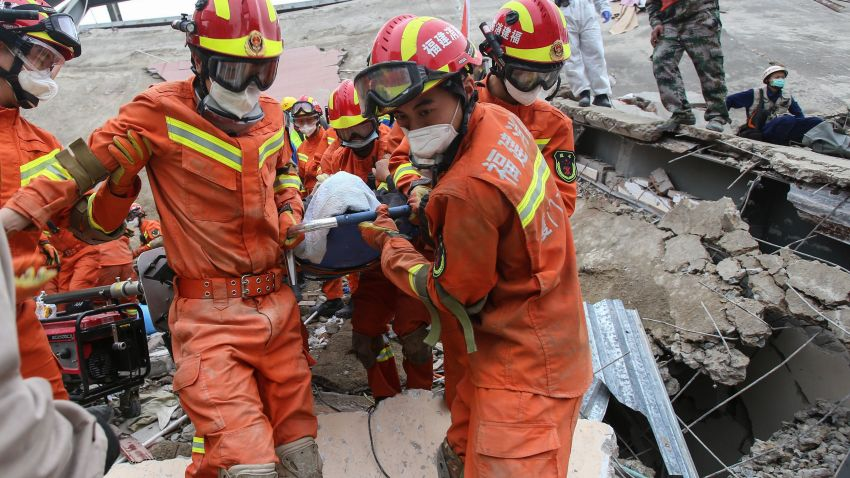 A man is rescued from the rubble of a collapsed hotel