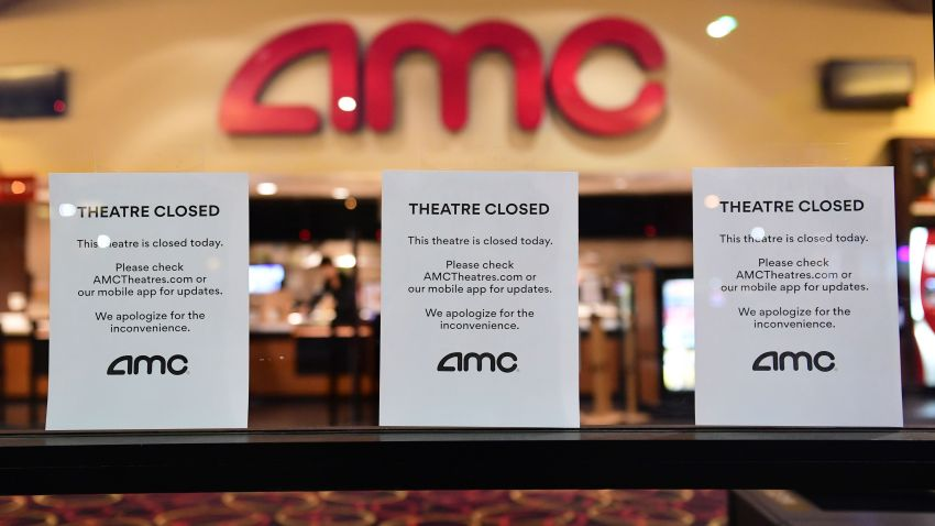 """""""Theater Closed"""" signs are posted in front of an AMC movie theater"""