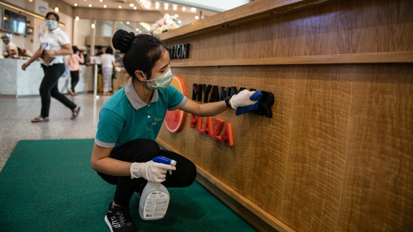 A staff wearing a face mask, amid concerns of the COVID-19 coronavirus, cleans the counter at a shopping center in Yangon on March 18, 2020.