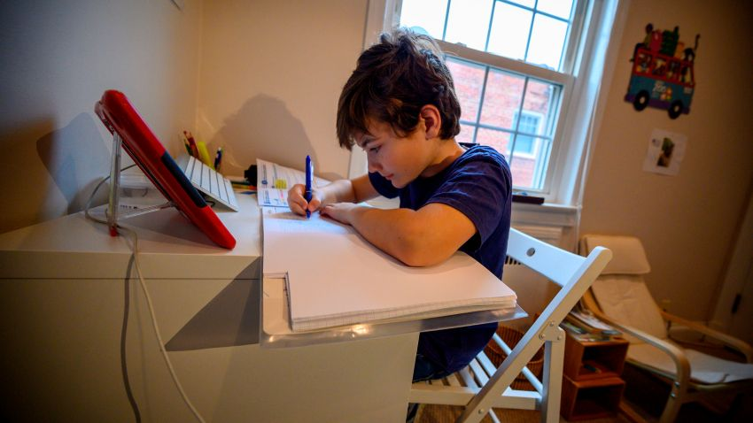 A boy does school work at home.
