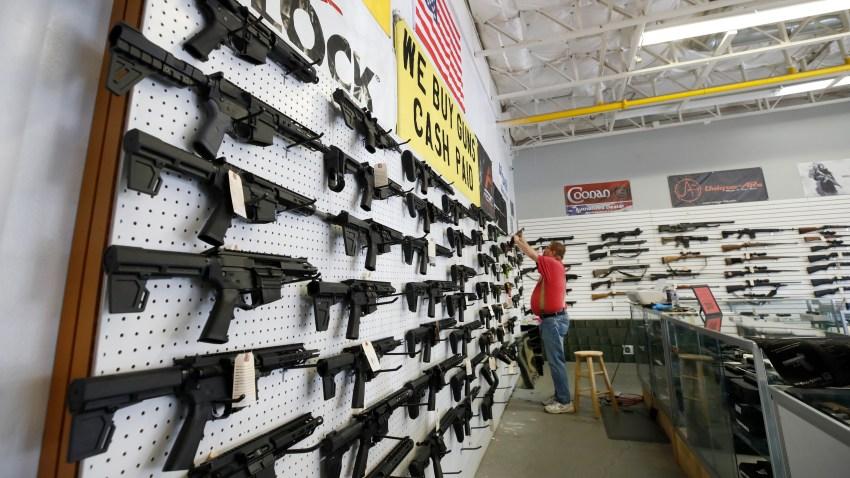 a worker restocks AR-15 guns