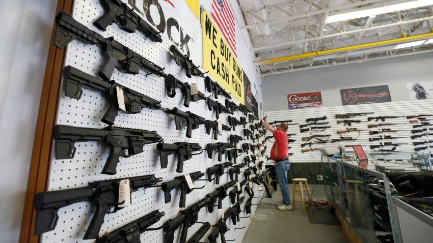 a worker restocks AR-15 guns