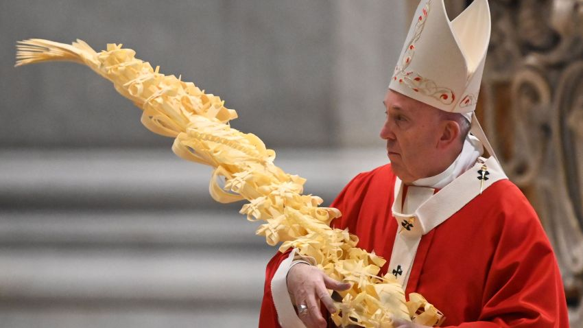 Pope Francis holds a palm branch as he celebrates Palm Sunday