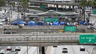 A man rides a bike past tents on an overpass above a freeway.