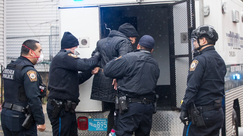 masked officers of the Chelsea Police Department in Chelsea, Massachusetts help a suspect into the back of a police truck
