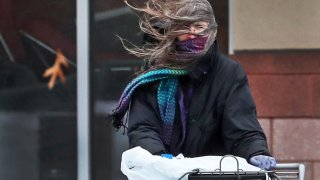A shopper struggles with the wind.