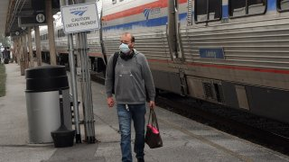 A passenger wearing a protective face mask arrives in Orlando, Florida on a nearly empty southbound Amtrak train on April 15, 2020.