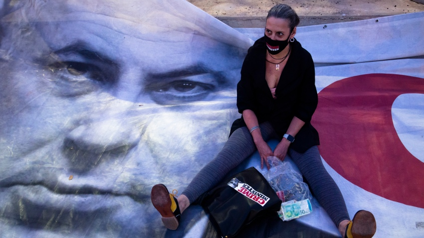 A woman sits on a placard showing Israeli Prime Minister Benjamin Netanyahu