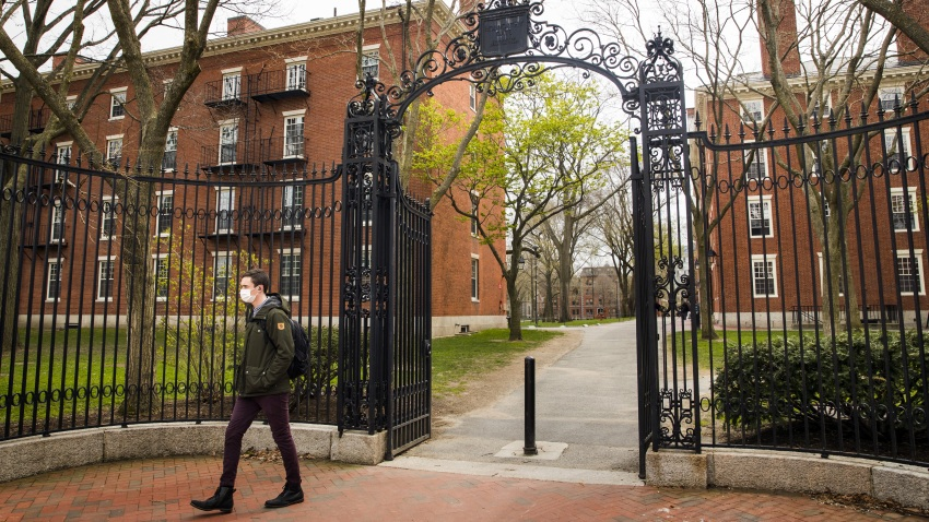 A pedestrian wearing a protective mask exits Harvard Yard on the closed Harvard University campus in Cambridge, Massachusetts, U.S., on Monday, April 20, 2020. College financial aid offices are bracing for a spike in appeals from students finding that the aid packages they were offered for next year are no longer enough after the coronavirus pandemic cost their parents jobs or income.