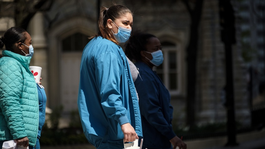 Health care workers wearing protective masks hold take-out food in Chicago