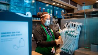 In this May 12, 2020, file photo, a Starbucks employee wears a face shield and mask as she makes a coffee in Ronald Reagan Washington National Airport in Arlington, Virginia.
