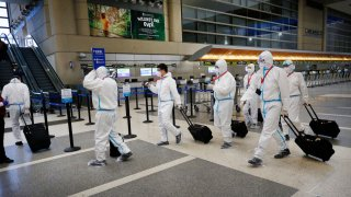 In this May 11, 2020, file photo, the flight crew for a Hainan Airlines flight walks through the Tom Bradley International Terminal, Los Angeles International Airport (LAX), which is now requiring travelers to wear face coverings to help keep fellow passengers and crew safe.