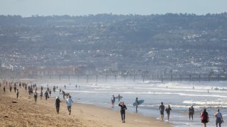 People walk on Manhattan Beach May 13, 2020 in Southern California.