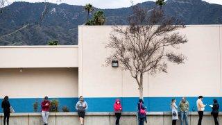 People wait in line outside a DMV office.