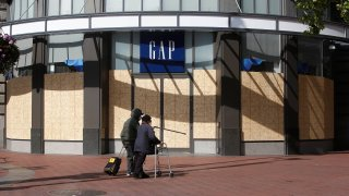 Pedestrians wearing masks walk past a boarded up Gap store