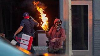A man throws a molotov cocktail.