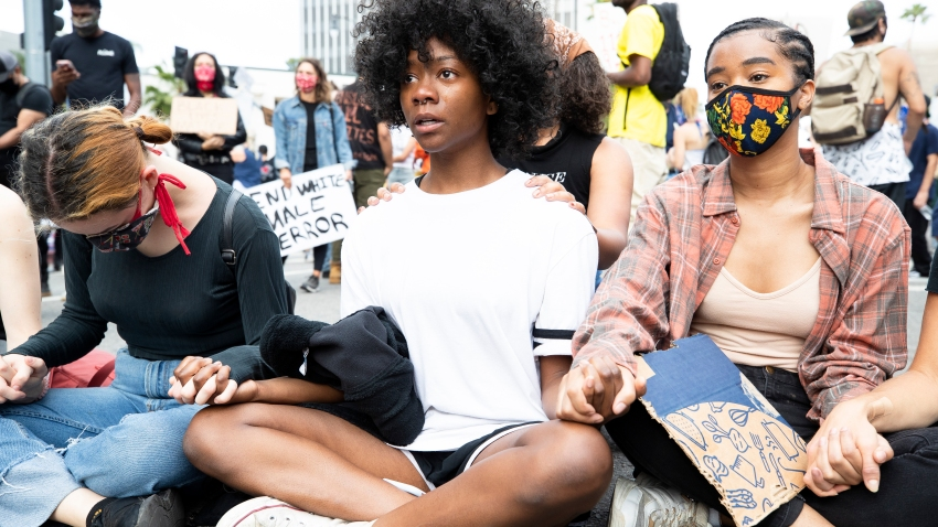 Demonstrators sit holding hands during a march in response to George Floyd's death on June 2, 2020 in Los Angeles, California.