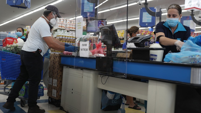 Lay Guzman stands behind a partial protective plastic screen and wears a mask and gloves as she works as a cashier at the Presidente Supermarket on April 13, 2020 in Miami, Florida.