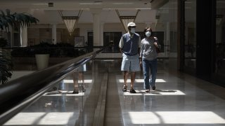 Shoppers wearing protective masks walk at a mall.