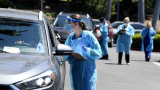 In this April 24, 2020, file photo, workers wearing personal protective equipment (PPE) perform drive-up COVID-19 testing administered from a car at Mend Urgent Care testing site for the coronavirus at the Westfield Culver City.