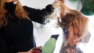 Hair stylist blow drying hair